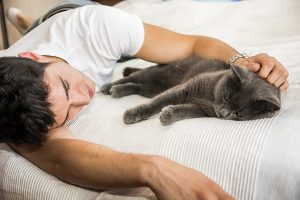Handsome Young Man Cuddling his Gray Cat Pet